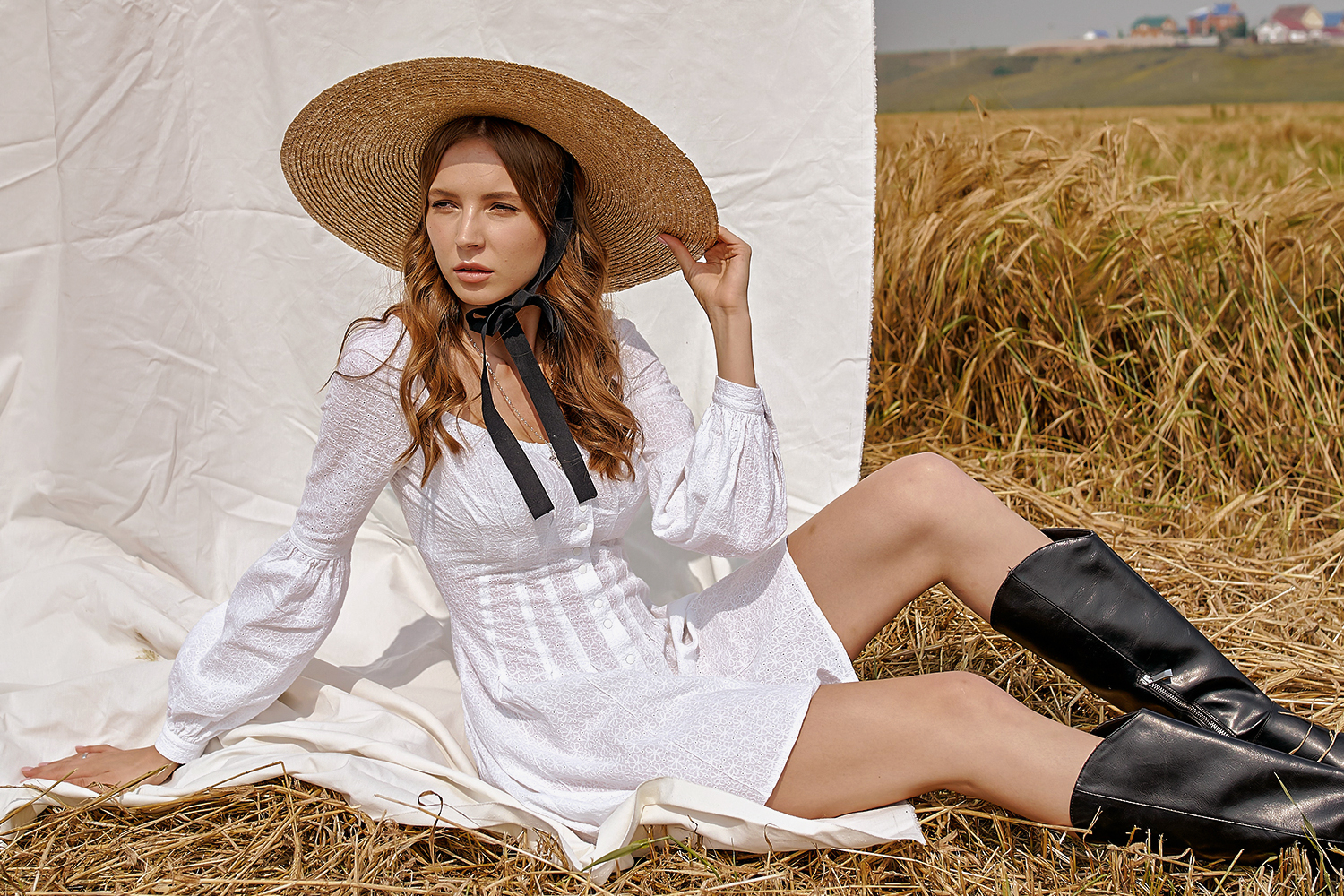 young woman in knee-lenght boots and short dresss is posing in the field