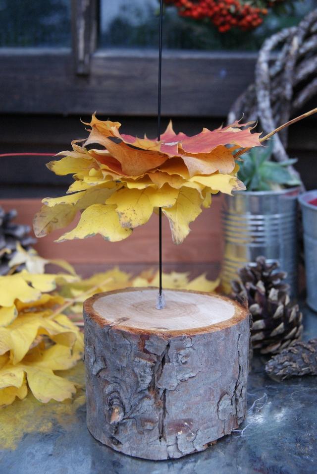 DIY bunte Herbstblätter auf einen Steckdraht fädeln - ein Holzstamm dient als Basis