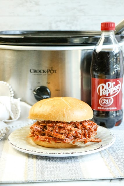 sandwich and dr pepper bottle in front of slow cooker