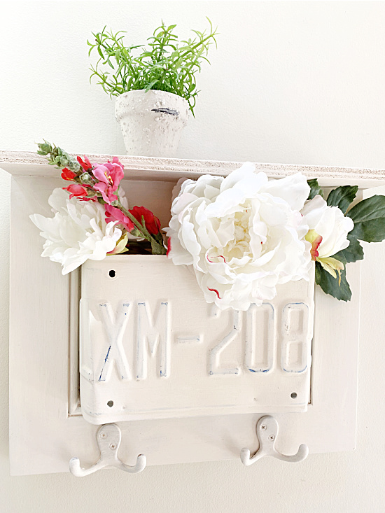 License plate shelf with hooks filled with flowers