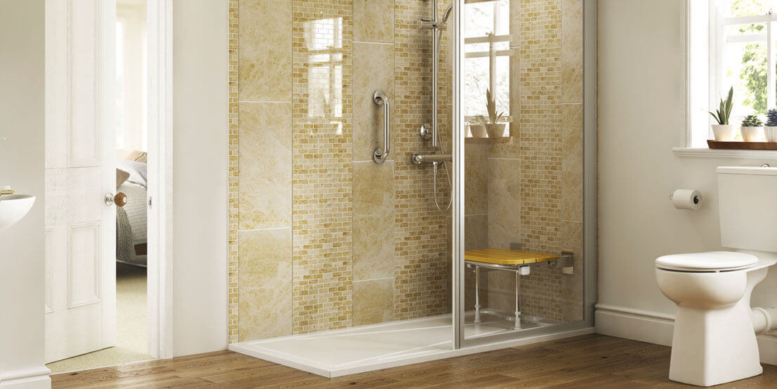 An image of an accessible bathroom. There is a large walk in shower with a fold down seat and grab handles. A toilet is also visible.