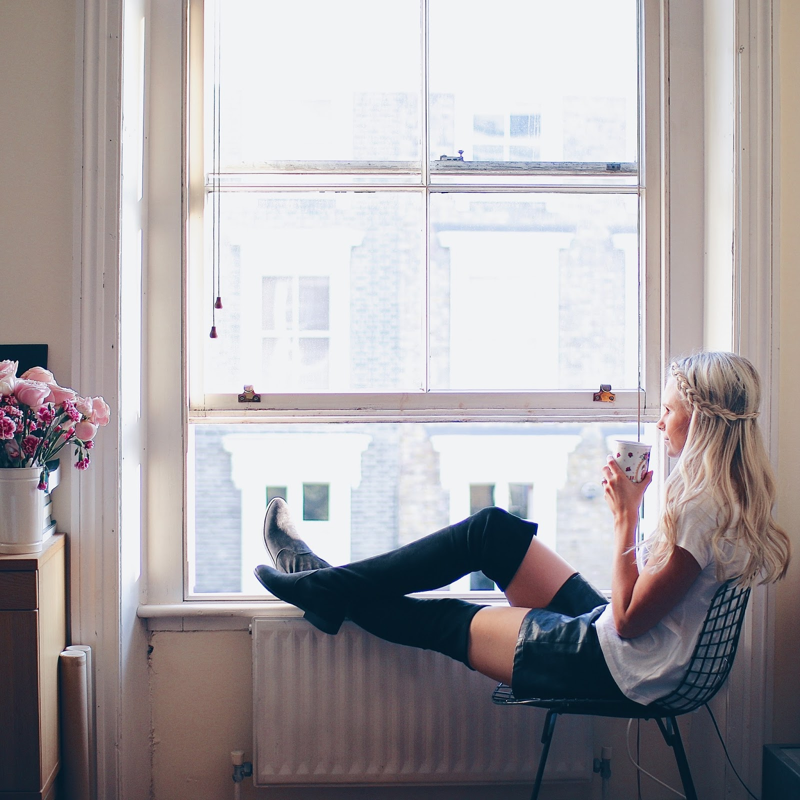 women in over the knee boots sitting on window sill of notting hill london flat