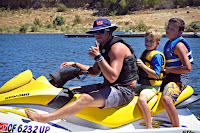 "Camp Counselor Travis Cassidy gives ""thumbs up sign"" while driving two happy campers around Castic Lake on a jet ski."