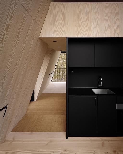 cocina al interior de la cabaña con mueble oscuro y madera clara alrededor