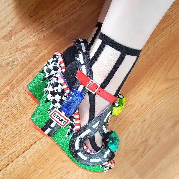 wearing wedge shoes with toy racing cars and green glitter grass