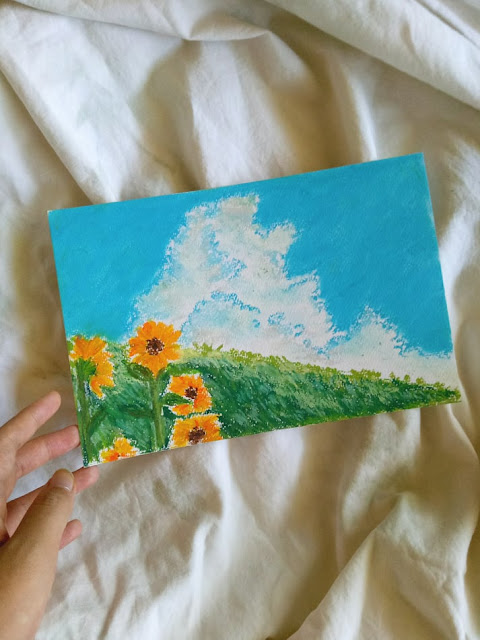Oil pastel artwork of nature scenery: sunflowers, a field of grass, and the bright blue sky