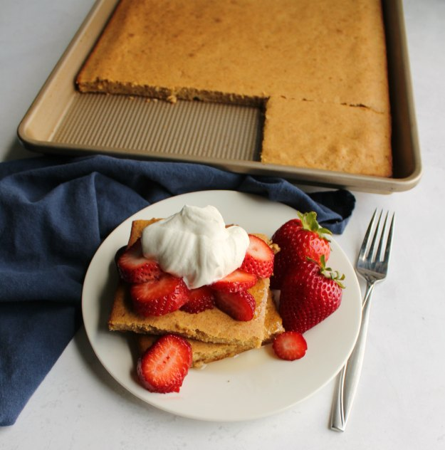 small plate with 2 slices sheet pan pancake, sliced strawberries and maple whipped cream