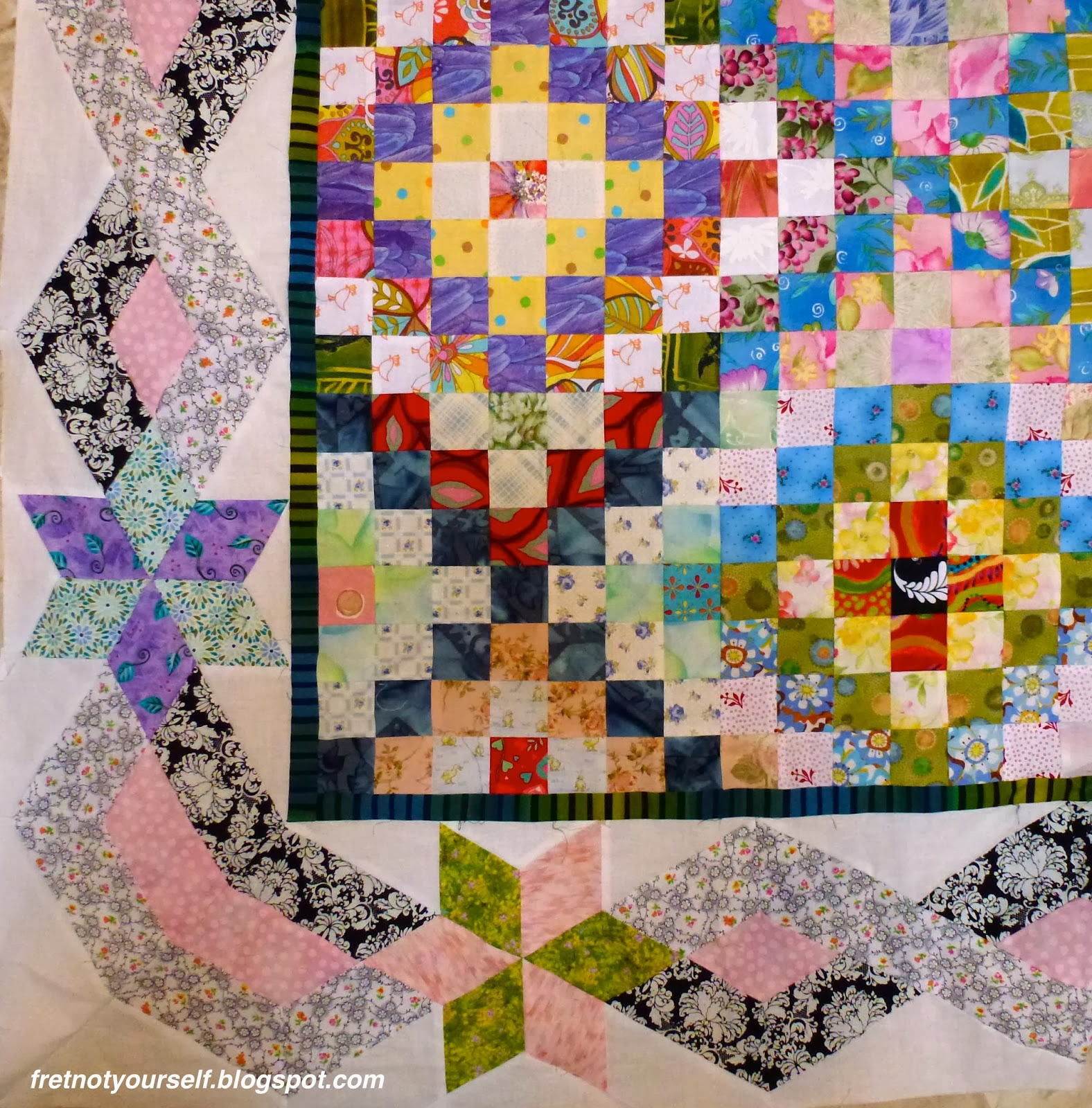 Multi-colored quilt in a Trip Around the World variation; narrow green and black inner border; larger outer border of stars with braided black and white fabrics.