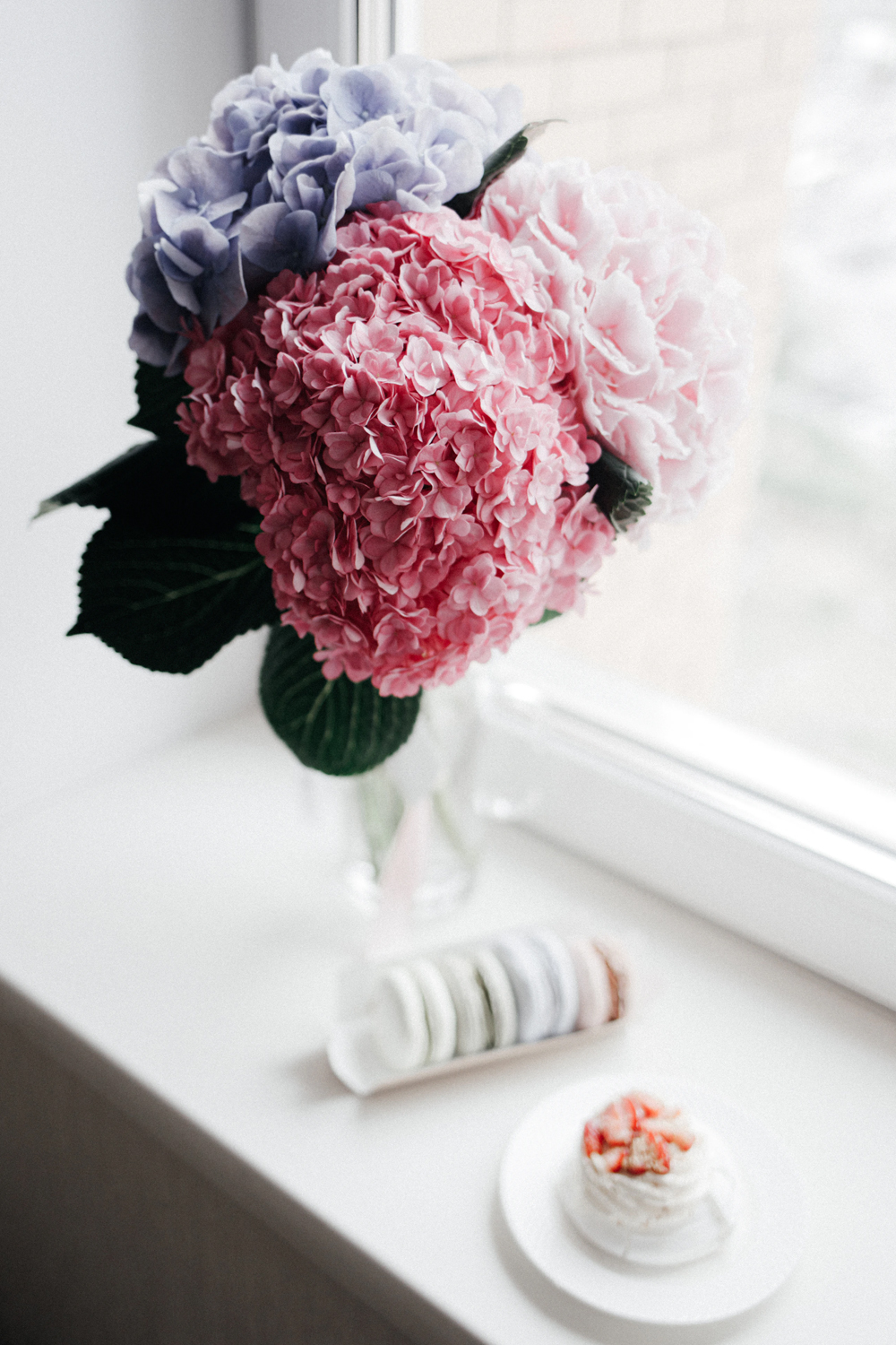 a bouquet of Hydrangeas on the window close to the cup of tea