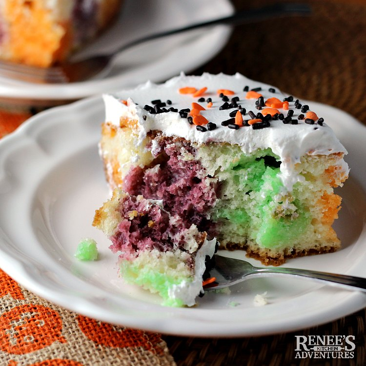 Piece of Halloween Jello Poke Cake by Renee's Kitchen Adventures on a white plate with a bite on the fork ready to eat