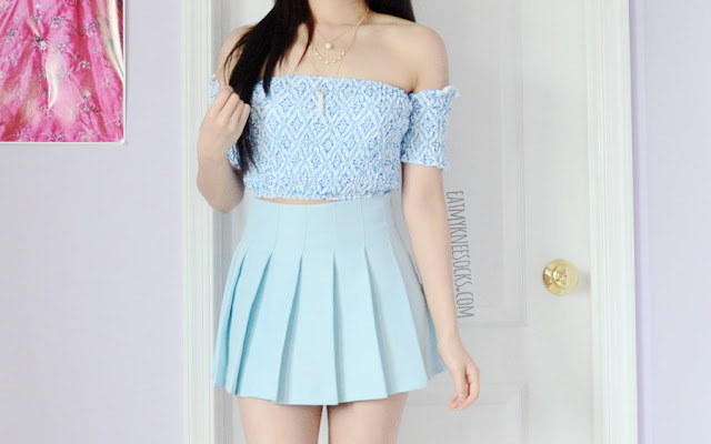 A pastel, summer outfit featuring a light sky blue pleated tennis skirt from Fusion Republic, cropped off-shoulder geometric tribal top from Dresslink, and layered necklace.