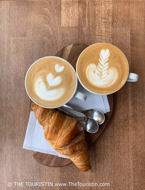 Two cups of espresso-based drinks next to a croissant served on a small wooden tray placed on a wooden table.