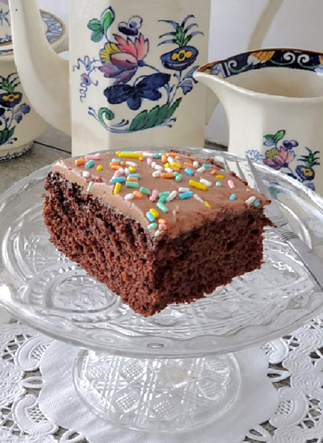 this is a slice of chocolate mayo cake on a crystal plate with vintage coffee pot in the back with blue flowers