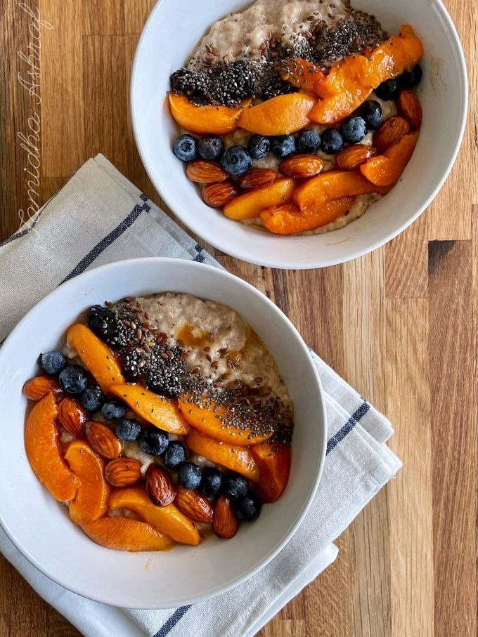 two bowl of oatmeal topped with roasted apricots and nuts