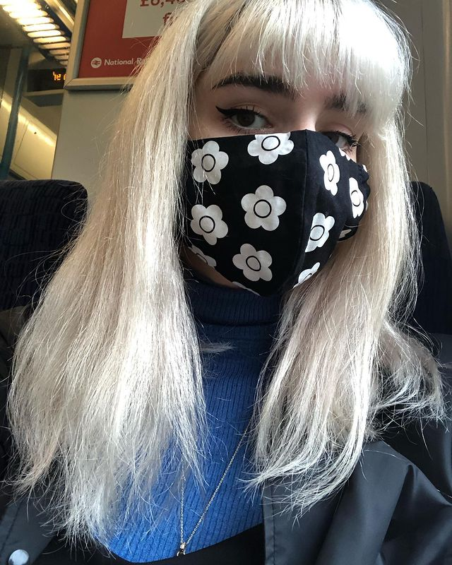 Me wearing a face mask printed with Mary Quant daisies