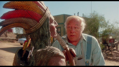 Ray Spruce (George Kennedy) stands outside his shop looking at a wooden Indian statue in a Creepshow 2 (1987) movie scene