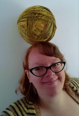 Balancing giant ball of yarn on head