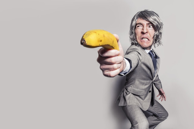 grey haired young man in grey suit defensively holding out a banana like a sword