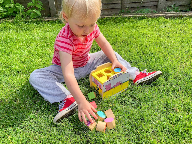 Toddler reaching out for coloured blocks to put in yellow wooden peppa pig campervan shape sorter