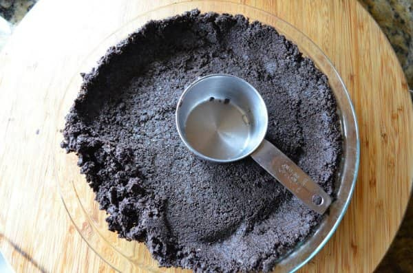 Homemade Oreo Cookie Crust in a pie plate for no bake peanut butter pie recipe.