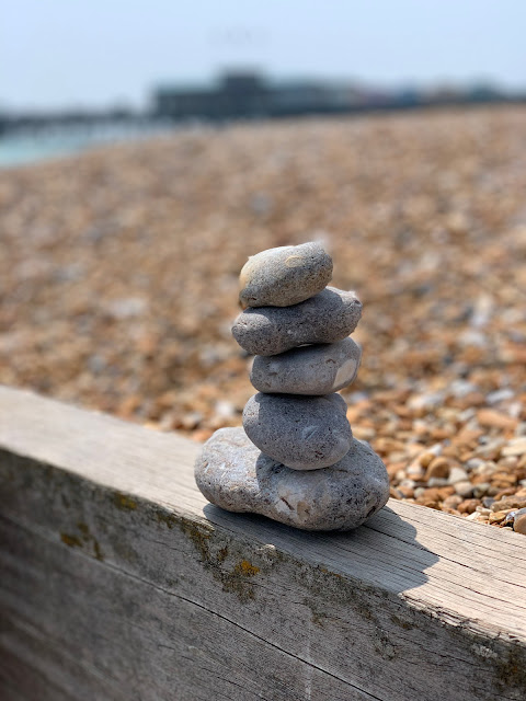 stone pile on Hastings Beach with Hastings pier in background