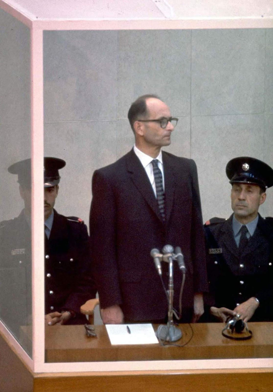 Nazi war criminal Adolf Eichmann standing in a protective glass booth during his trial in Israel in 1961. Eichmann was convicted for his role in organizing and carrying out the Holocaust and ultimately executed.