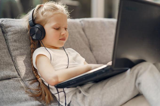 Menina no sofá usando headphone e com laptop no colo