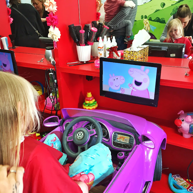 4 year old girl sitting in a car getting her haircut and watching Peppa Pig