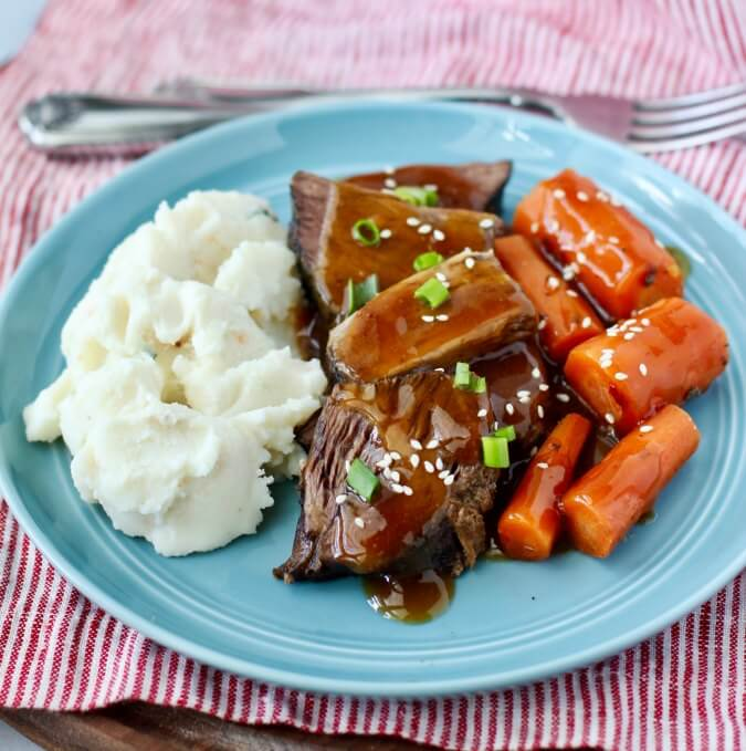 Slow Cooker Asian Pot Roast on a plate with carrots and mashed potatoes