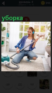 Девушка в наушниках с помощью пылесоса делает уборку в квартире