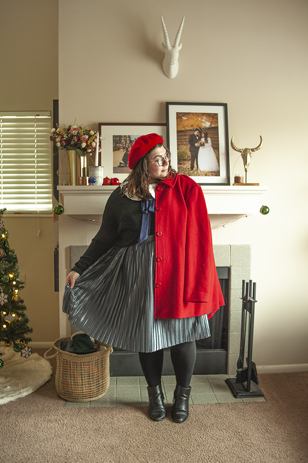 An outfit consisting of a wide white ruffled peter pan collar with a navy blue ribbon tied underneath it, a black sweater tucked into blue silver pleated midi skirt, a red beret and red coat with black Chelsea boots.