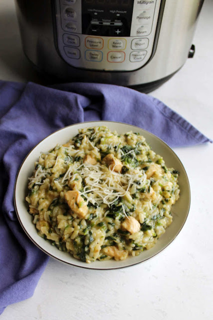 bowl of creamy spinach and chicken risotto with cheese on top in front of instant pot