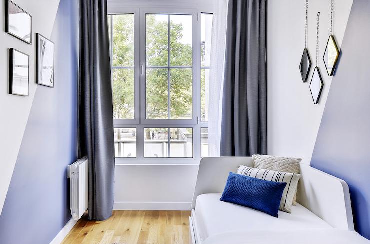 Dormitorio de invitados con pared pintada en azul y blanco con efecto triángulo.