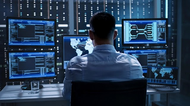 A man in a shirt sitting in front of 6 black and blue screens with data on it.