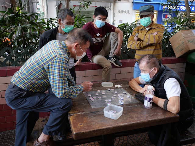 Men playing and watching xiangqi while wearing surgical masks