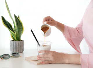 Woman pouring honey into cup