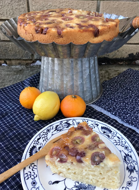 Side view of a cake stand with a finished grape upside down cake and a slice of finished cale on a small plate in front.