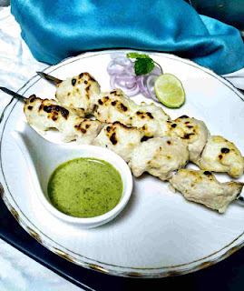 Chicken malai kebab Shewer on a plate with green chutney and onion slices