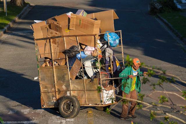 Catador de papel puxando carrinho bem carregado