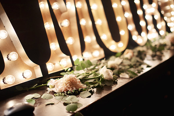 Details: scattered greenery and cafe au lait dahlias and other florals decorate marquee lights that spell out AMOUR rented from Bespoke Decor