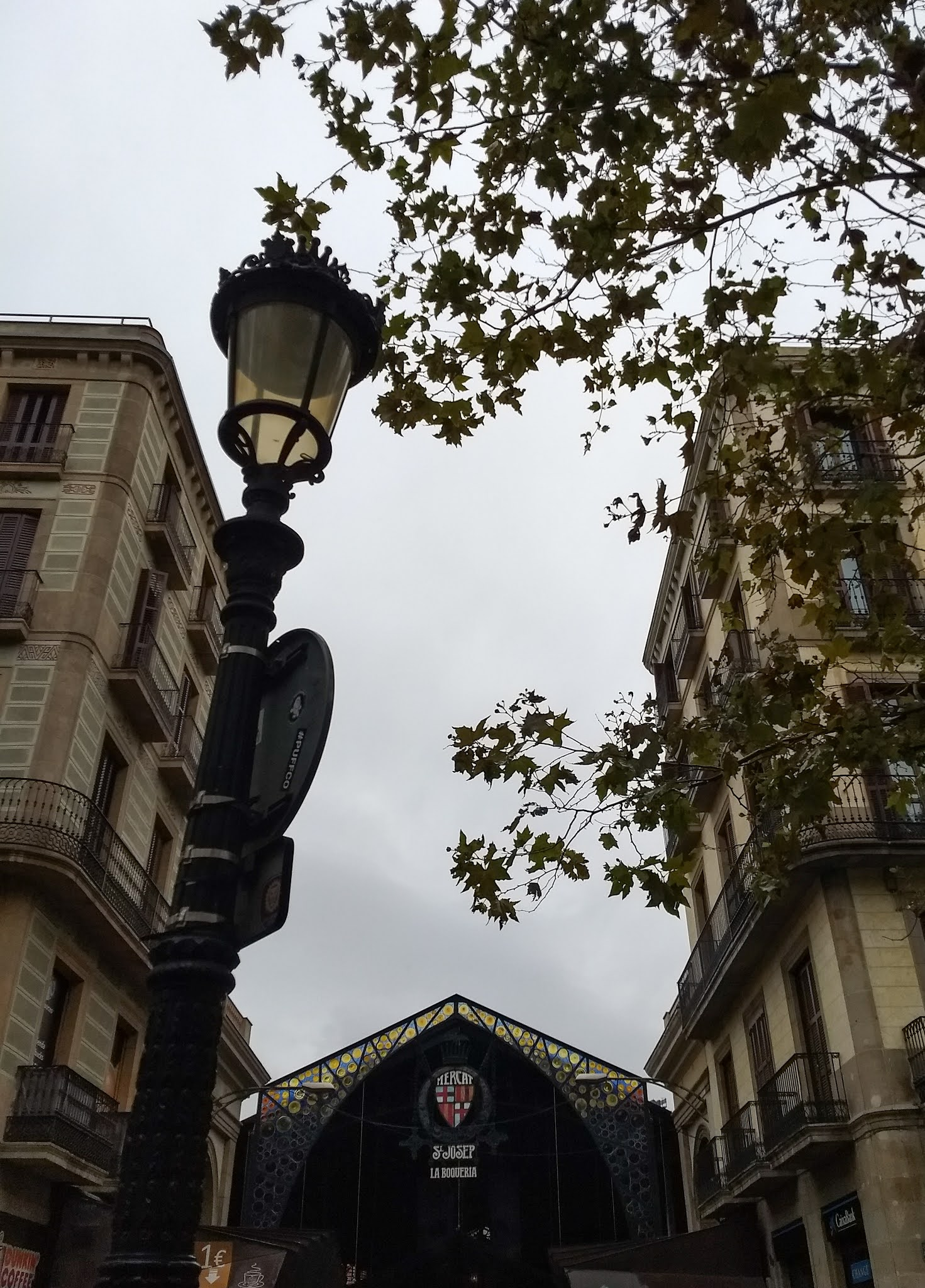 View of an entrance to Mercado de La Boqueria with trees and a lamp post in the foreground.