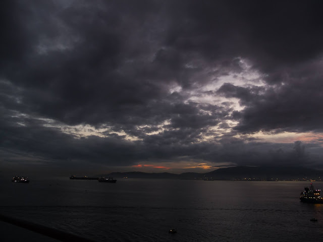 Dark twilight clouds in the port of Gibraltar with a faint sunset in the background.