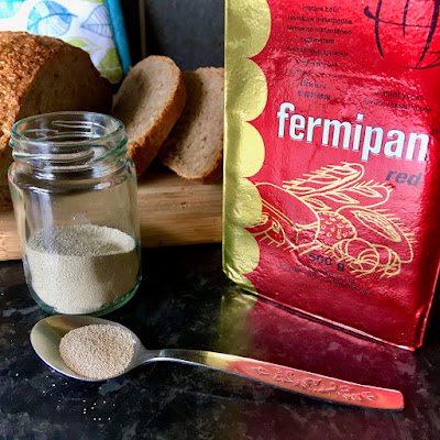 Fermipan yeast in a packet and a jar with a loaf of bread in the background