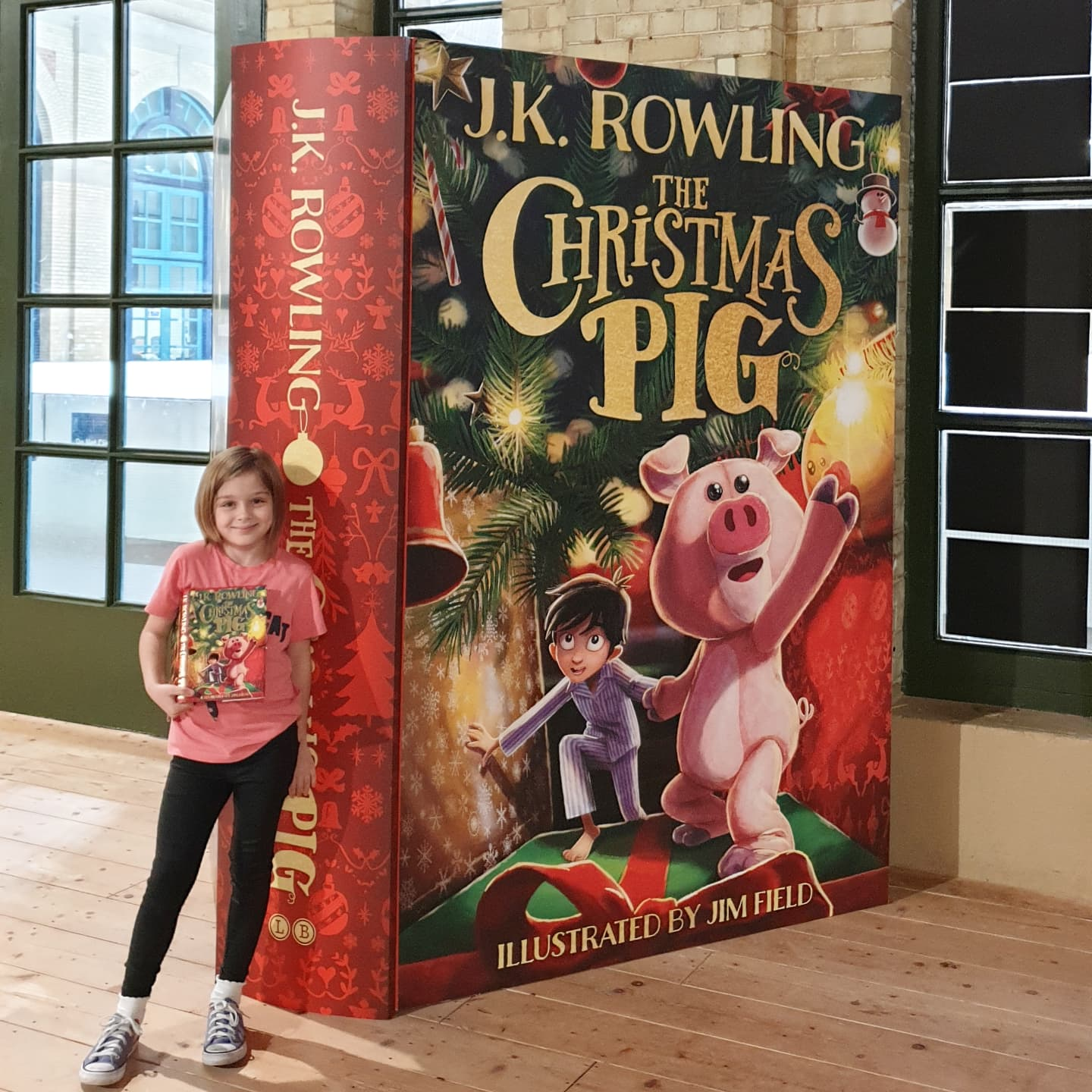 girl standing in front of a giant christmas pig book