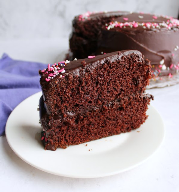 slice of chocolate layer cake with shiny chocolate frosting and sprinkles