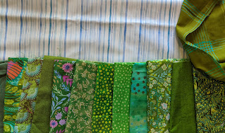 A variety of green prints against the blue and white striped background