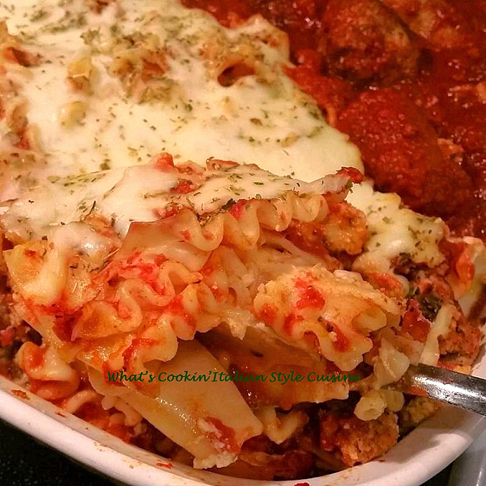 this is a lasagna pasta layered with meat sauce and melted mozzarella cheese on a white dish with meatballs and sausage