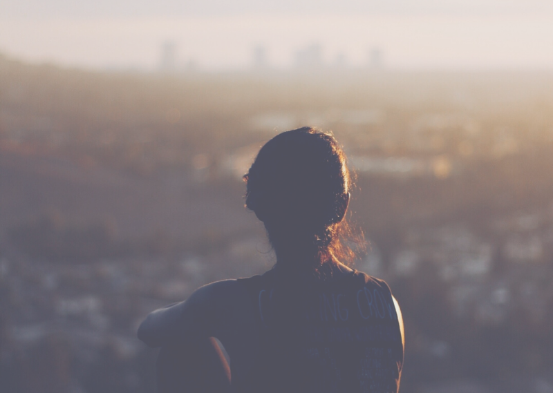 Lady looking a the city view in a post about 15 easy self-care ideas you can start today.