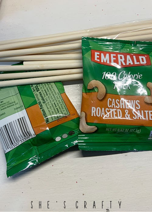 How to make a birthday bouquet - tape dowels to back of cashew packages.