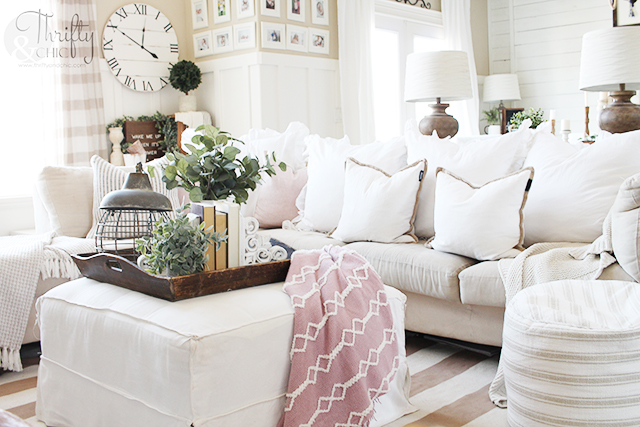 living room with white couch, ottoman, striped rug and pink blanket